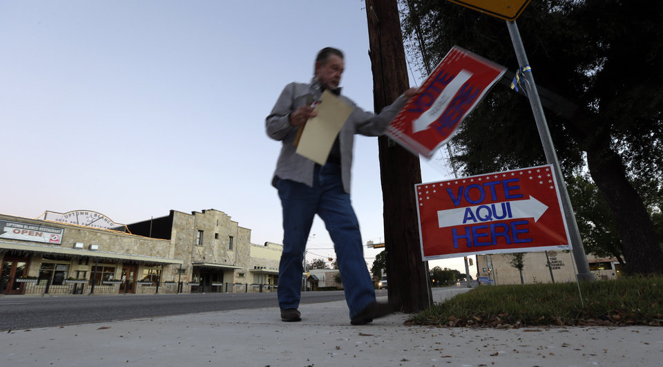 Alternate election clerk Van Downing posts signs prior to the polls opening Tuesday, Nov. 6, 2012, on the downtown square in Blanco, Texas. (AP Photo/Eric Gay)