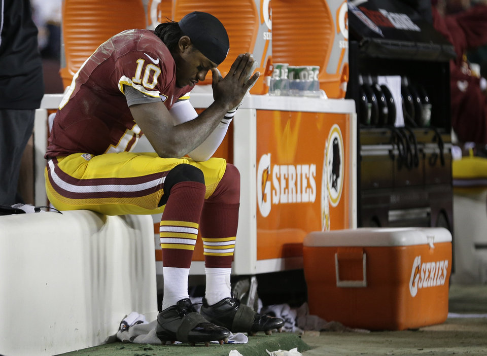 Washington Redskins quarterback Robert Griffin III sits on the bench after being injured during an NFL wild card playoff football game against the Seattle Seahawks in Landover, Md., Sunday, Jan. 6, 2013. The Seahawks defeated the Redskins 24-14. (AP Photo/Evan Vucci)