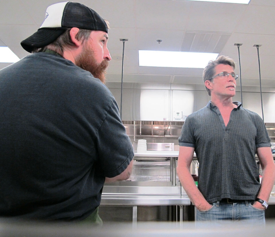 Photo - Chefs Josh Valentine, left, and Rick Bayless discuss plans with Jonathon Stranger (out of view) at the Francis Tuttle School of Culinary Arts on Sunday in preparation for the OK Chefs Relief pop-up on Monday.  DAVE CATHEY - THE OKLAHOMAN