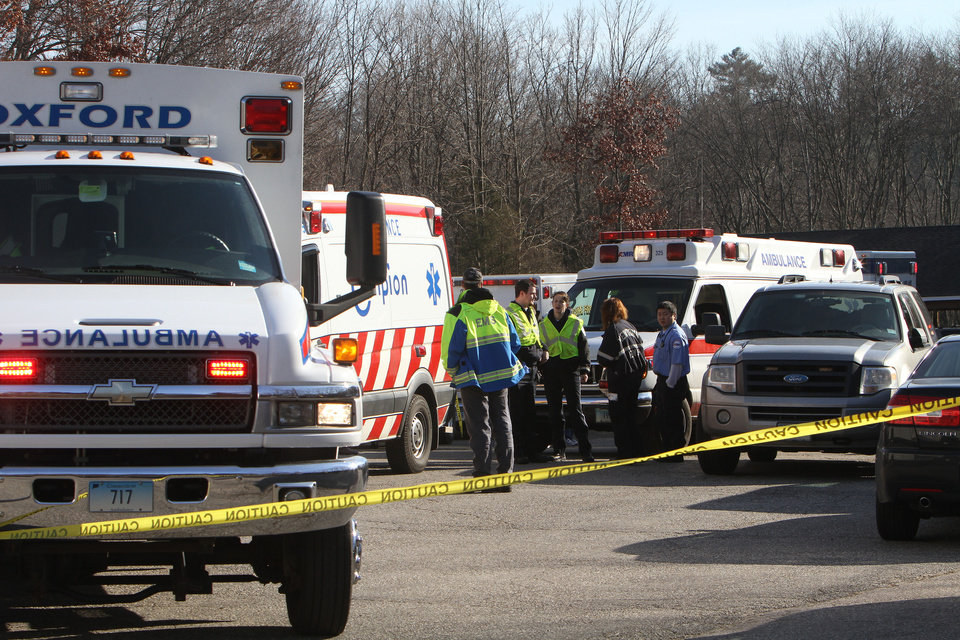 Photo - Emergency personnel work the scene outside Sandy Hook Elementary School in Newtown, Conn. where authorities say a gunman opened fire, leaving 27 people dead, including 20 children, Friday, Dec. 14, 2012.. (AP Photo/The Journal News, Frank Becerra Jr.) MANDATORY CREDIT, NYC OUT, NO SALES, TV OUT, NEWSDAY OUT; MAGS OUT ORG XMIT: NYWHI107