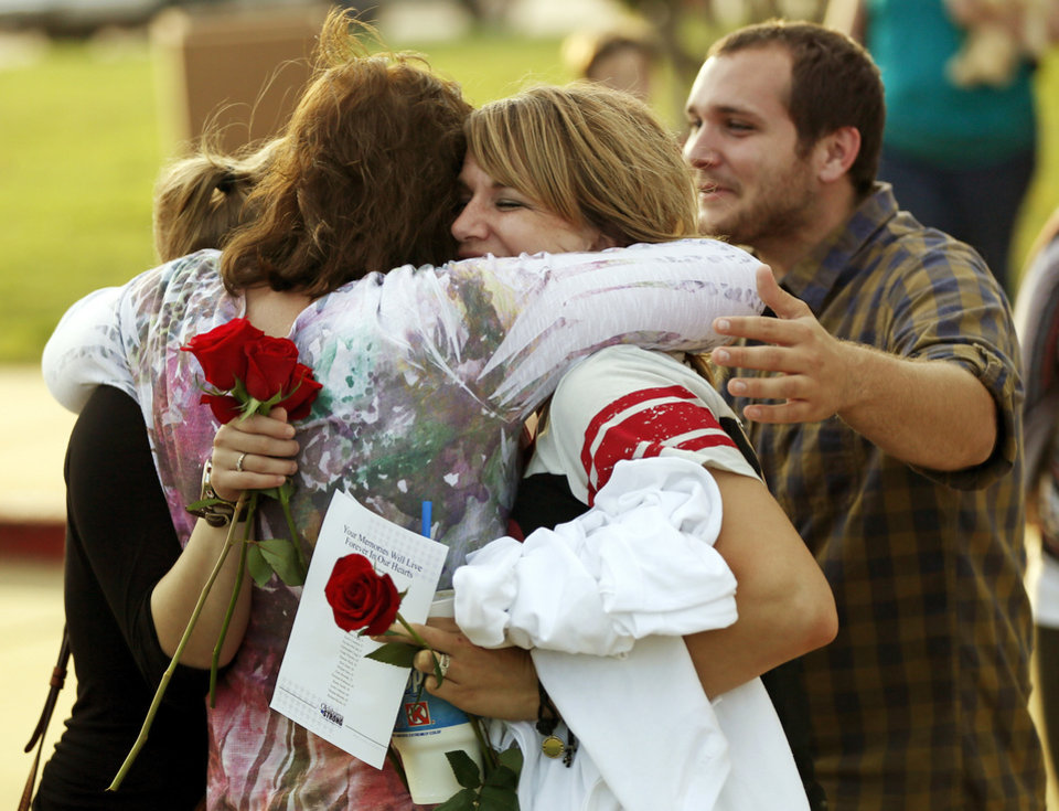 Photo - Teacher's assistant Megan Williams, second from right, hugs bus driver Cindy McReynolds with teacher Kelly McAlister, left, and teacher's assistant Chad Russell, right, after Oklahoma Strong: Coming Together in Faith, a memorial prayers service for the victims of recent Oklahoma tornadoes, at First Baptist Church in Moore Okla., Sunday, May 26, 2013. The teachers and assistants were attending the memorial, while McReynolds was driving a shuttle. They all work at Apple Creek Elementary and rode out the Moore tornado in a bathroom together. Photo by Nate Billings, The Oklahoman