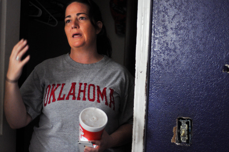 Photo - Summer Roberts shows the closet where she initially hid in the house before leaving before the tornado hit. Preparing for the worst, Roberts took a 2 liter of Diet Coke and Mountain Dew, a box of powdered doughnuts and a bag of funyuns into the closet. Photo by KT King, The Oklahoman