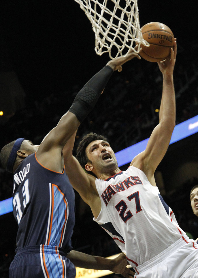 Atlanta Hawks power forward Zaza Pachulia (27) goes up for a shot as Charlotte Bobcats center Brendan Haywood (33) defends in the first half of an NBA basketball game Wednesday, Nov. 28, 2012 in Atlanta. (AP Photo/John Bazemore)
