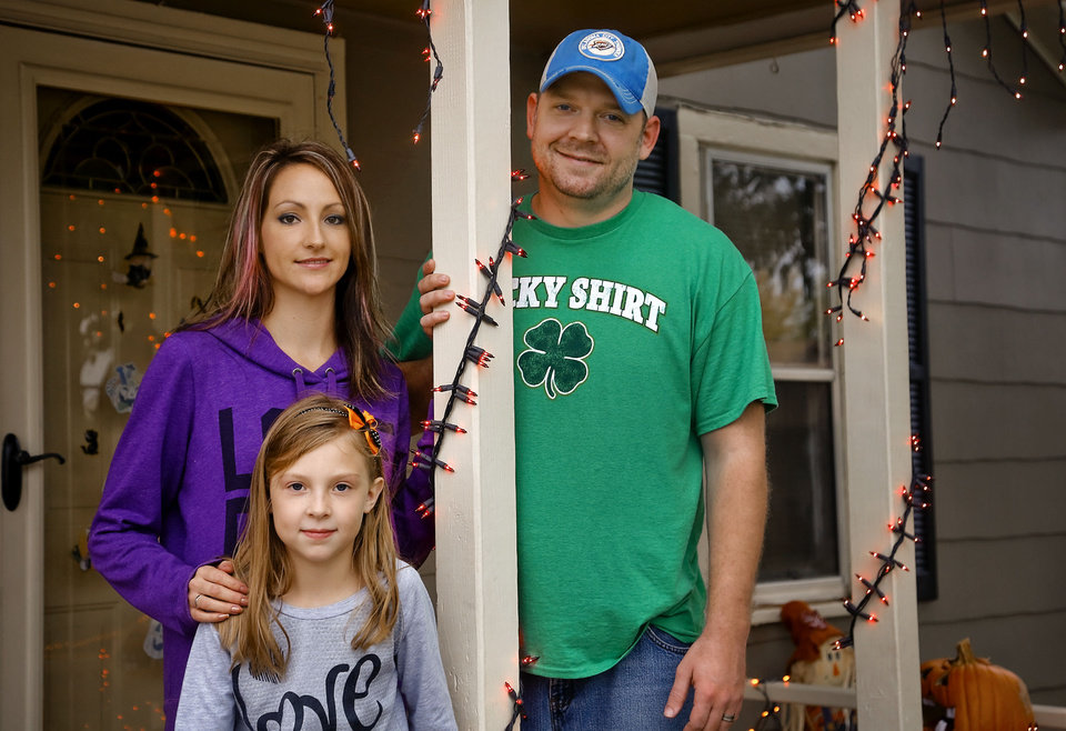 Photo - Jamie, Rustee and Rusty Wilson, from left, pose for a photo at their home in Valley Brook on Wednesday. The family is opposed to the opening of an all-nude strip club in town. They're concerned about the potential crime growth.  CHRIS LANDSBERGER - The Oklahoman