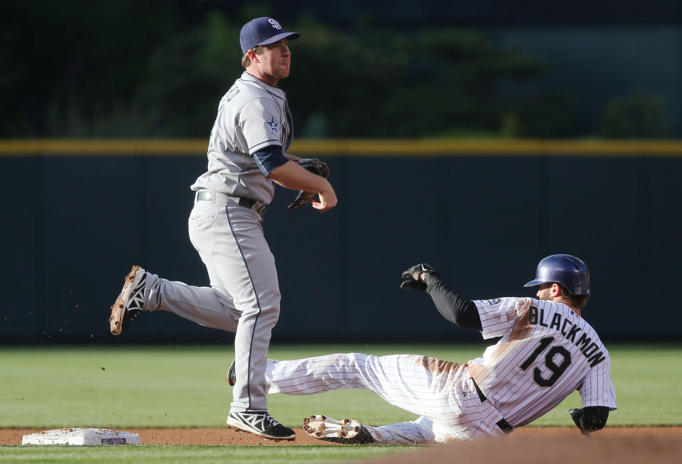 Photo - San Diego Padres second baseman Jedd Gyorko, left, throws to first base after forcing out Colorado Rockies' Charlie Blackmon at second base on the front end of a double play hit into by Drew Stubbs in the first inning of a baseball game in Denver on Saturday, May 17, 2014. (AP Photo/David Zalubowski)