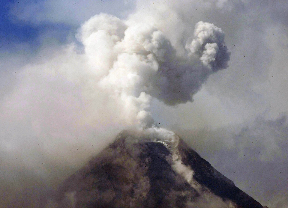 Photo - FILE - In this Dec. 23, 2009 file photo, a column of ash shoots up to the sky in a mild eruption of the cloud-covered Mayon volcano as viewed from Legazpi city in Albay province, 500 kilometers southeast of Manila, Philippines. The volcano spewed huge rocks and ash early Tuesday, May 7, 2013 after a 3-year calm, killing four climbers and trapping others near the crater, officials said. (AP Photo/Bullit Marquez, File)