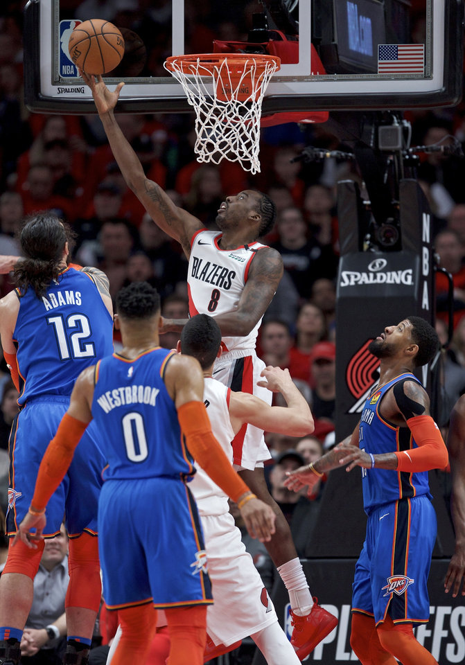 Photo - Portland Trail Blazers forward Al-Farouq Aminu, center, shoots between Oklahoma City Thunder center Steven Adams, left, and forward Paul George, right, during the first half of Game 2 of an NBA basketball first-round playoff series Tuesday, April 16, 2019, in Portland, Ore. (AP Photo/Craig Mitchelldyer)