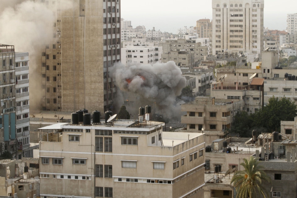 Photo -   Smoke is seen from an explosion by a high rise housing media organizations in Gaza City, Monday, Nov. 19, 2012. It's the Israel's military second strike on the building in two days. The Hamas TV station, Al Aqsa, is located on the top floor. (AP Photo/Hatem Moussa)