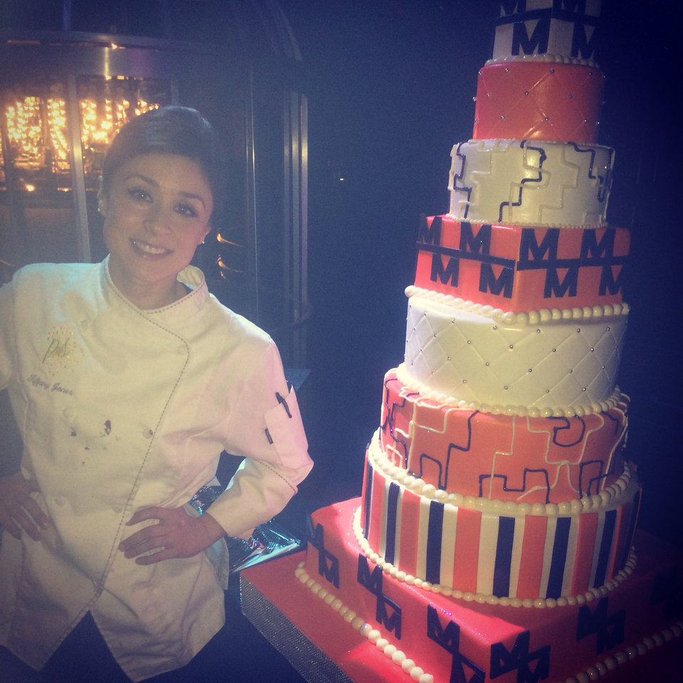 Photo - This undated photo provided by Tiffany Jones and posted in May 2014 to the Instagram account of her company, Peridot Sweets Las Vegas, shows Jones, left, with one of her creations, an 8-tier cake made for Morrow Meadows. Peridot Sweets' Twitter and Facebook accounts are set to automatically update from the shots of wedding cakes, macarons and cupcakes she posts on Instagram. (AP Photo/Courtesy Tiffany Jones)