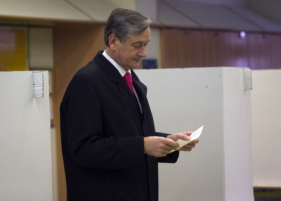 Photo -   Slovenian President Danilo Turk holds his ballot to cast it at a polling station in Ljubljana, Slovenia, Sunday, Nov. 11, 2012. Three candidates, including Turk, are vying for the presidency in Slovenia, a tiny, economically troubled European Union nation that is riven by deep political divisions and is in danger of needing a bailout. (AP Photo/Darko Bandic)