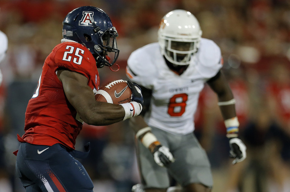Photo - Arizona's Ka'Deem Carey (25) looks to get by Oklahoma State's Daytawion Lowe (8) during the college football game between the University  of Arizona and Oklahoma State University at Arizona Stadium in Tucson, Ariz.,  Saturday, Sept. 8, 2012. Photo by Sarah Phipps, The Oklahoman