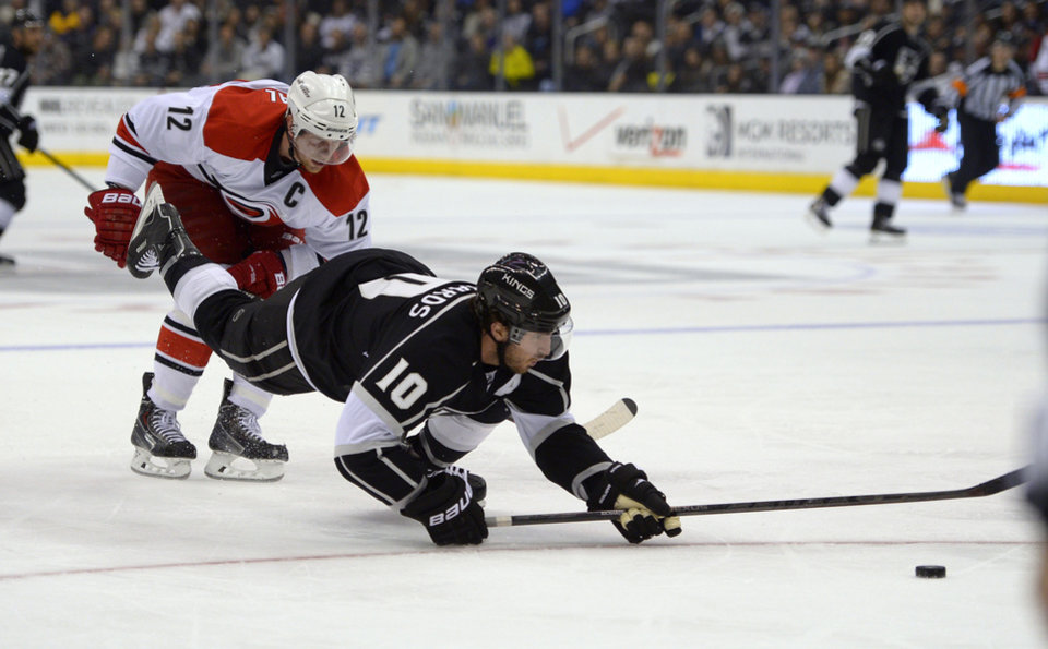 Photo - Los Angeles Kings center Mike Richards, front, is tripped by Carolina Hurricanes center Eric Staal during the second period of an NHL hockey game, Saturday, March 1, 2014, in Los Angeles. (AP Photo/Mark J. Terrill)