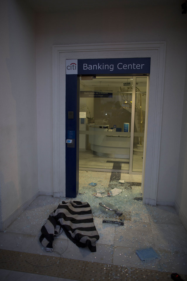 Photo - The glass door of a bank lies shattered after protesters threw rocks in Sao Paulo, Brazil, Thursday, June 19, 2014.  Some vandalism occurred as a protest in Brazil's biggest city that is hosting a World Cup match drew upward of 2,000 people. The protest in Sao Paulo was called by the Free Fare movement, the group that was behind the first protests last year that sparked roiling anti-government demonstrations across Brazil.(AP Photo/Dario Lopez-Mills)