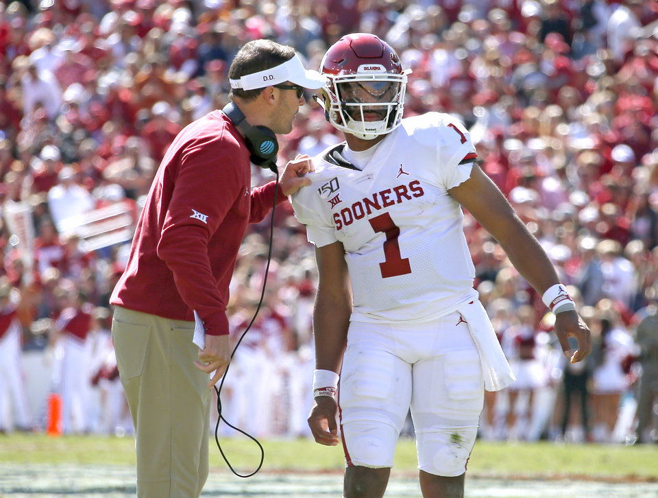Photo - Oklahoma head coach Lincoln Riley talks with Oklahoma's Jalen Hurts (1) in the second quarter during the Red River Showdown college football game between the University of Oklahoma Sooners (OU) and the Texas Longhorns (UT) at Cotton Bowl Stadium in Dallas, Saturday, Oct. 12, 2019. OU won 34-27. [Sarah Phipps/The Oklahoman]