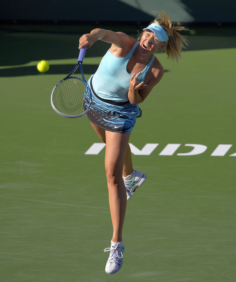 Photo - Maria Sharapova, of Russia, serves to Camila Giorgi, of Italy, during a third round match at the BNP Paribas Open tennis tournament, Monday, March 10, 2014 in Indian Wells, Calif. (AP Photo/Mark J. Terrill)