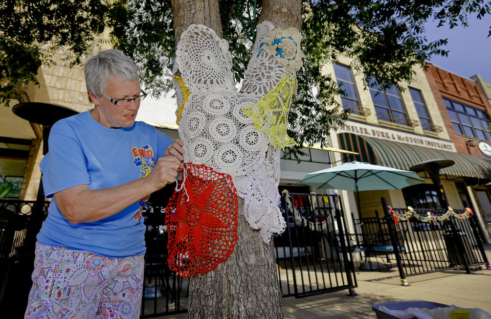 Photo - Paula Nightengale stitches together doilies around a tree for the Yarnover Enid community art event on Friday, Sept. 6, 2013 in Enid, Okla. The public art project was established to bring the town together to display 'art graffiti' created from items made and donated by the community.  Photo by Chris Landsberger, The Oklahoman