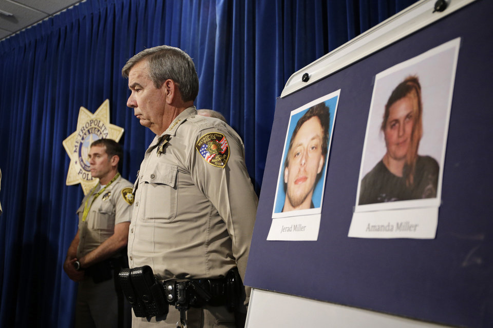 Photo - Las Vegas Sheriff Doug Gillespie stands by a board with the pictures of suspects Jerad Miller and Amanda Miller during a news conference Monday, June 9, 2014 in Las Vegas. Two police officers were having lunch at a strip mall pizza buffet when the Millers fatally shot them in a point-blank ambush, then fled to a nearby Wal-Mart where they killed a third person and then themselves in an apparent suicide pact, authorities said. (AP Photo/John Locher)