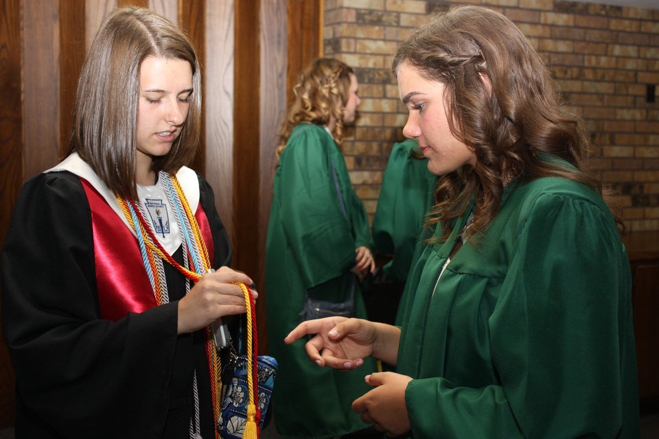 Photo -  Norman High School senior Elizabeth Waters, left, and Norman North senior Ashlyn Gardner decipher cord colors while waiting for baccalaureate services to begin at First Baptist Church. PHOTO BY LYNETTE LOBBAN, FOR THE OKLAHOMAN
