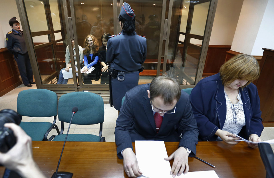 Photo -   CORRECTS LEFT TO RIGHT Feminist punk group Pussy Riot members, from left, Yekaterina Samutsevich, Maria Alekhina, and Nadezhda Tolokonnikova sit in a glass cage at a court room in in Moscow, Wednesday Oct. 10, 2012. Lawyers Violetta Volkova, right, and Lev Lyalin, foreground center, defending members of feminist punk group Pussy Riot, sit in front. (AP Photo/Sergey Ponomarev)