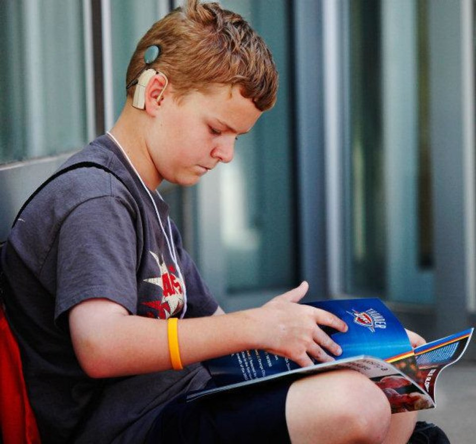Photo - Peter Hardt, 11, thumbs through a new book after visiting the Thunder Book Bus. Hardt wears a cochlear implant. The bus visit was part of the weeklong Hearts for Hearing summer camp in downtown Oklahoma City this week. Photo by Jim Beckel, The Oklahoman  JIM BECKEL