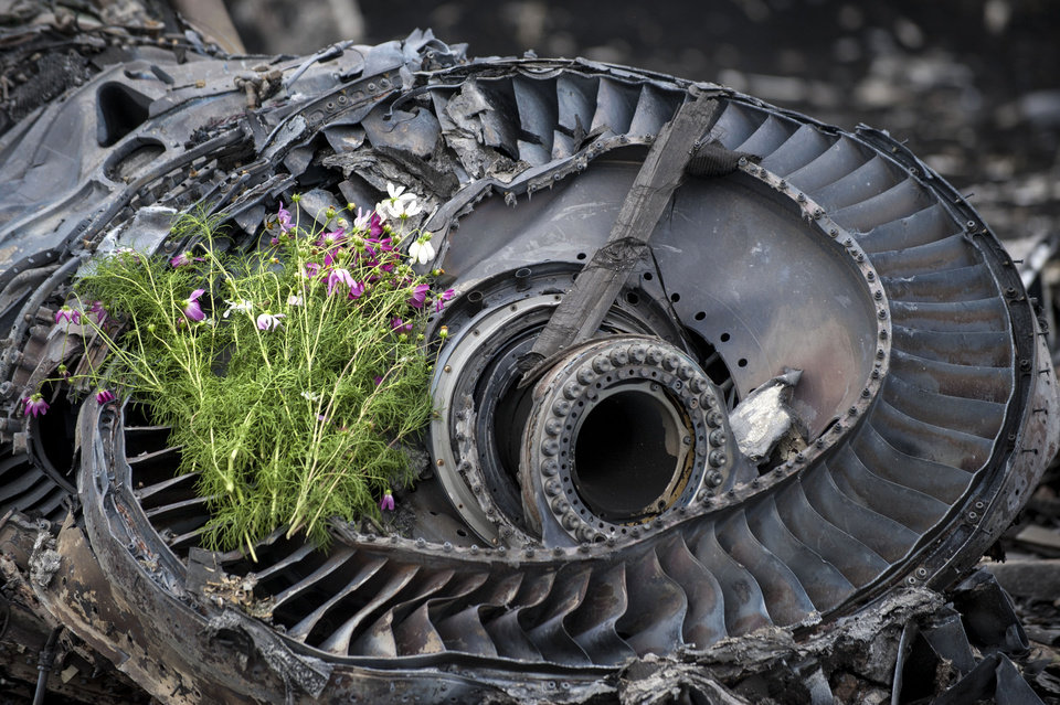 Photo - Wildflowers are placed on a plane engine at the crash site of a Malaysia Airlines jet near the village of Hrabove, eastern Ukraine, Saturday, July 19, 2014. World leaders demanded Friday that pro-Russia rebels who control the eastern Ukraine crash site of Malaysia Airlines Flight 17 give immediate, unfettered access to independent investigators to determine who shot down the plane. (AP Photo/Evgeniy Maloletka)