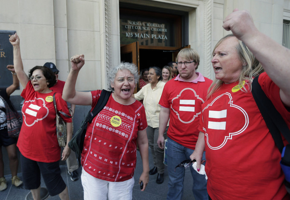 Photo - Supporters celebrate after a non-discrimination ordinance was passed by the San Antonio city council, Thursday, Sept. 5, 2013, in San Antonio. The ordinance in part will prohibit discrimination based on sexual orientation and gender identity.  (AP Photo/Eric Gay)