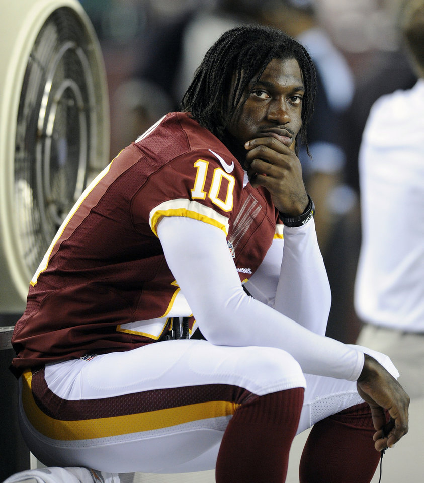 Washington Redskins quarterback Robert Griffin III sits on the bench during the first half of an NFL preseason football game with the Tampa Bay Buccaneers, Wednesday, Aug. 29, 2012, in Landover, Md. Griffin was not scheduled to play in the game. (AP Photo/Nick Wass) ORG XMIT: FDX120
