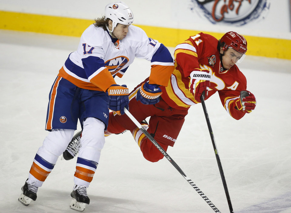 Photo - New York Islanders' Matt Martin, left, checks Calgary Flames' Mikael Backlund, from Sweden, during the first period of an NHL hockey game Friday, March 7, 2014, in Calgary, Alberta. (AP Photo/The Canadian Press, Jeff McIntosh)