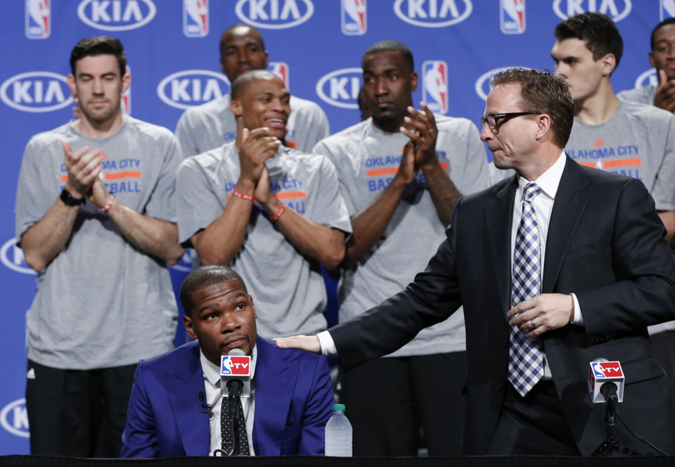 Photo - Oklahoma City Thunder head coach Scott Brooks, right, puts his hand on the shoulder of a teary-eyed Kevin Durant during the news conference announcing Durant is the winner of the 2013-14 Kia NBA Basketball Most Value Player Award in Oklahoma City, Tuesday, May 6, 2014. (AP Photo/Sue Ogrocki)