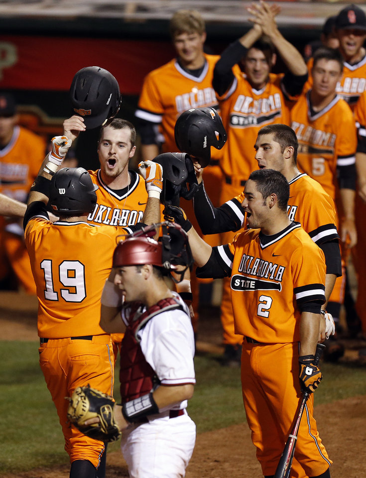 Photo - Oklahoma State celebrate a 3-run home run by Aaron Cornell (19) in the eighth inning near Oklahoma catcher Anthony Hermelyn (9) during an NCAA baseball game between Oklahoma and Oklahoma State in the Big 12 baseball tournament at the Chickasaw Bricktown Ballpark in Oklahoma City, Friday, May 23, 2014. (AP Photo/ The Oklahoman, Nate Billings)
