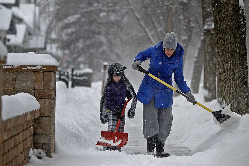 Amy Wolf and her daughter Audrey Wolf, 6,  shovel the sidewalk on Friday, Feb.  22, 2013 in Minneapolis.   A major snowstorm that buried parts of the Midwest grazed southern Minnesota, where two to three inches of snow snarled the morning commute in the Twin Cities area. (AP Photo/The Star Tribune, Elizabeth Flores)  MANDATORY CREDIT; ST. PAUL PIONEER PRESS OUT; MAGS OUT; TWIN CITIES TV OUT