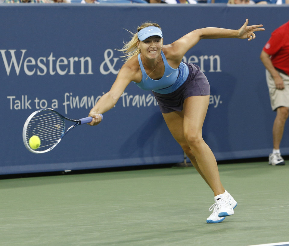 Photo - Maria Sharapova, from Russia, returns a volley to Ana Ivanovic, from Serbia, during a semifinal match at the Western & Southern Open tennis tournament, Saturday, Aug. 16, 2014, in Mason, Ohio. (AP Photo/David Kohl)