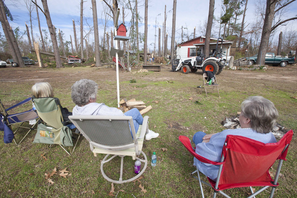 Three women sit in lawn chairs in a storm-damaged neighborhood in Fordyce, Ark., Monday, Jan. 23, 2012. The National Weather Service says no injuries or deaths were reported when high winds and suspected tornadoes struck the state Sunday night. (AP Photo/Danny Johnston) ORG XMIT: ARDJ105