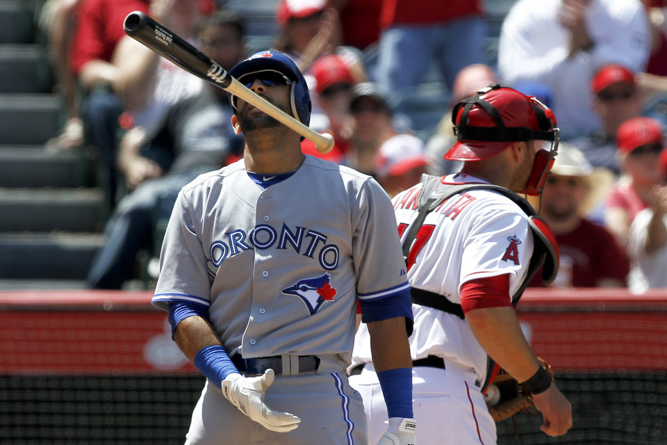 Photo -   Toronto Blue Jays' Jose Bautista, left, tosses his bat after striking out with a runner on base to end the top of the seventh inning as Los Angeles Angels catcher Chris Iannetta turns away during a baseball game in Anaheim, Calif., Sunday, May 6, 2012. (AP Photo/Chris Carlson)