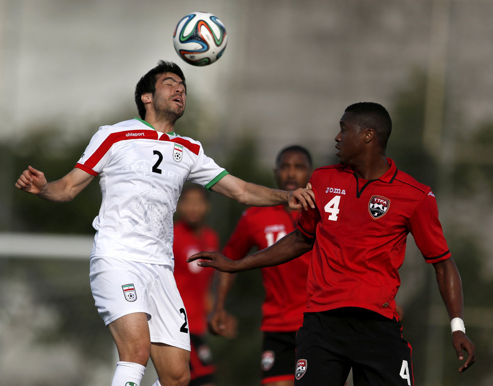 Photo - Iran's Khosrow Heidari, left, heads the ball while Trinidad and Tobago's Sheldon Bateau defends on the play during the first half of an international soccer friendly at the Corinthians soccer team training center Sao Paulo, Brazil, on Sunday, June 8, 2014. Iran will play in group F of the 2014 soccer World Cup. (AP Photo/Julio Cortez)
