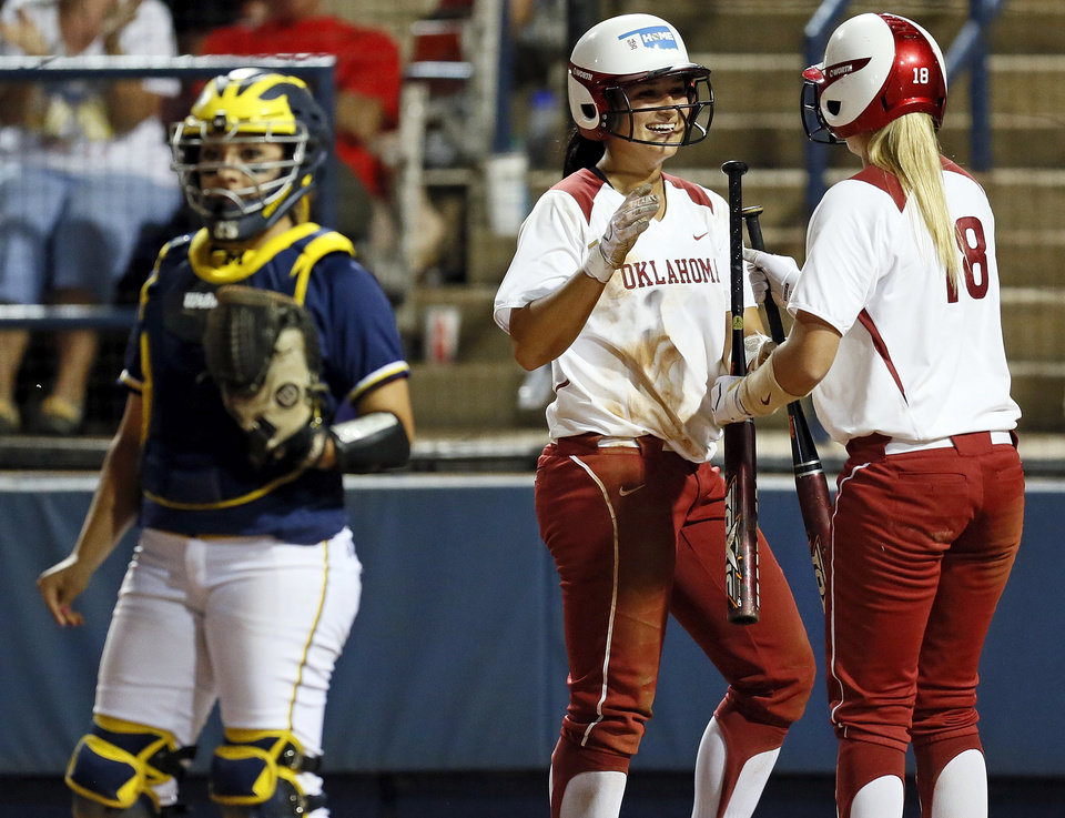 Photo - OU's Lauren Chamberlain (44) is greeted at home plate by Jessica Shults (18) in front of Michigan catcher Lauren Sweet (25) after Chamberlain scored in the third inning during an NCAA softball game in the Women's College World Series between Oklahoma and Michigan at ASA Hall of Fame Stadium, Thursday, May 30, 2013. Photo by Nate Billings, The Oklahoman