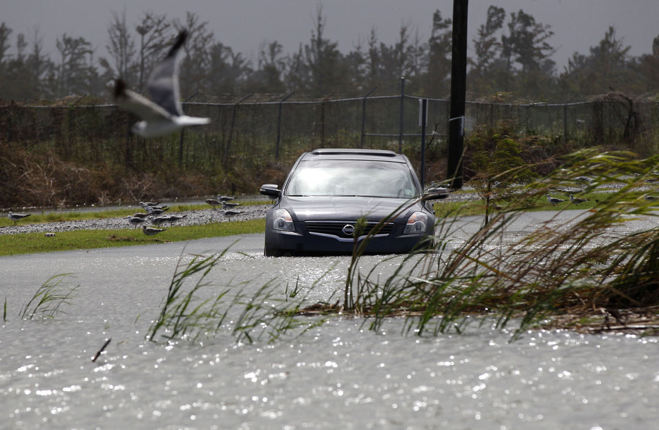 A car sits stranded in rising floodwaters from Isaac, which is expected to make landfall in the region as a hurricane this evening in Venice, La.,  the southernmost tip of the state, Tuesday, Aug. 28, 2012. Venice is outside the storm protection system and has been under mandatory evacuation. Forecasters at the National Hurricane Center warned that Isaac, especially if it strikes at high tide, could cause storm surges of up to 12 feet (3.6 meters) along the coasts of southeast Louisiana and Mississippi and up to 6 feet (1.8 meters) as far away as the Florida Panhandle. (AP Photo/Gerald Herbert) ORG XMIT: LAGH116