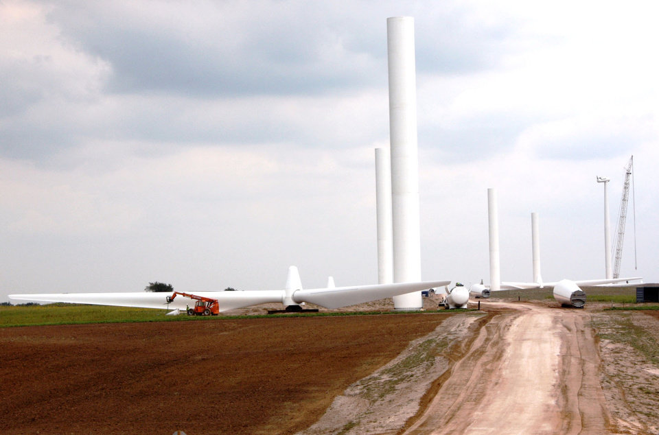 Photo - These photos provided by OG&E show the construction of the OU Spirit wind farm near Woodward on Sept. 17. Parts of wind turbines lay on the road ready to be put together. ORG XMIT: KOD