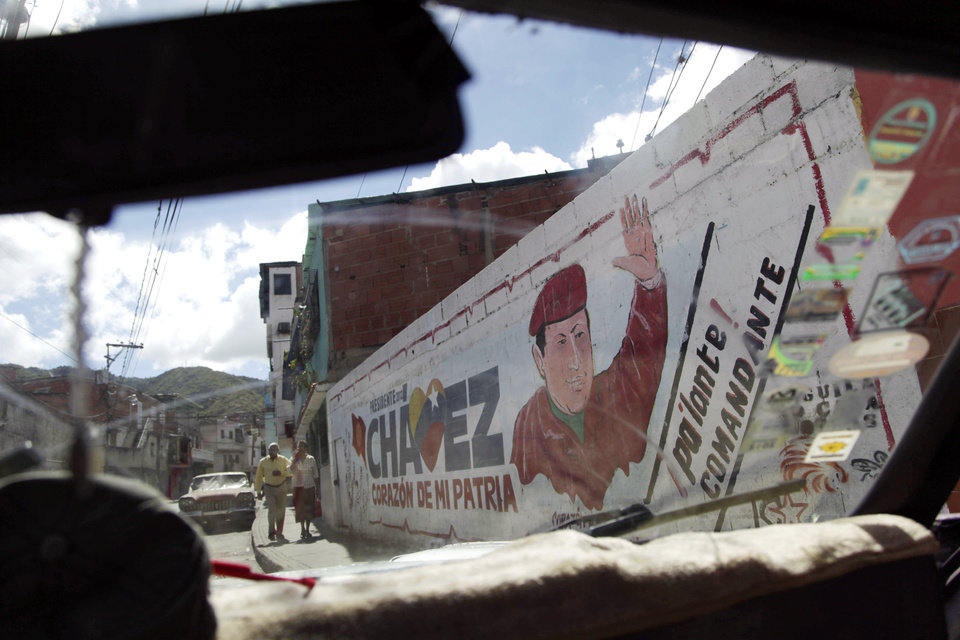 Photo - The windshield of a car frames a mural of Venezuela's President Hugo Chavez in Caracas, Venezuela, Wednesday, Jan. 2, 2013.  Venezuela's vice president is returning home Wednesday from a visit with Chavez in Cuba and says the ailing president's condition remains