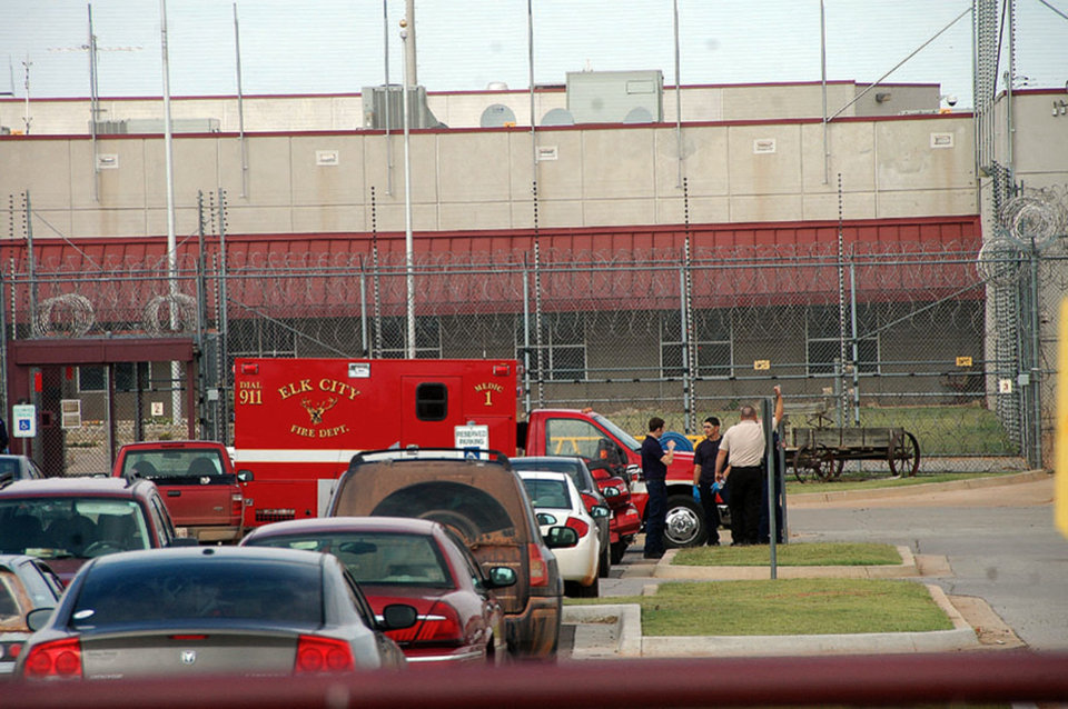 Photo - PRISON RIOT: Emergency vehicles an authorities standby at the entrance to the North Fork Corrections Facility in Sayre, Okla. Tuesday, Oct. 11, 2011.  Inmates were confined to their cells and their movements restricted after widespread fighting at an Oklahoma prison between black and Hispanic California inmates sent at least 46 inmates to the infirmary or hospitals before police and prison guards were able to restore order, authorities said Tuesday. (AP Photo/ Elk City Daily News, Jodi Davis) ORG XMIT: OKKJ105