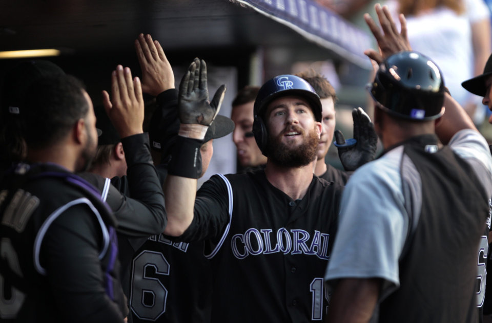 Photo - Colorado Rockies teammates and coaches congratulates Rockies' Charlie Blackmon (19) in the dugout after Blackmon's two-run home run in the third inning of a baseball game against the San Diego Padres in Denver on Tuesday, July 8, 2014. Colorado won 2-1.(AP Photo/Joe Mahoney)