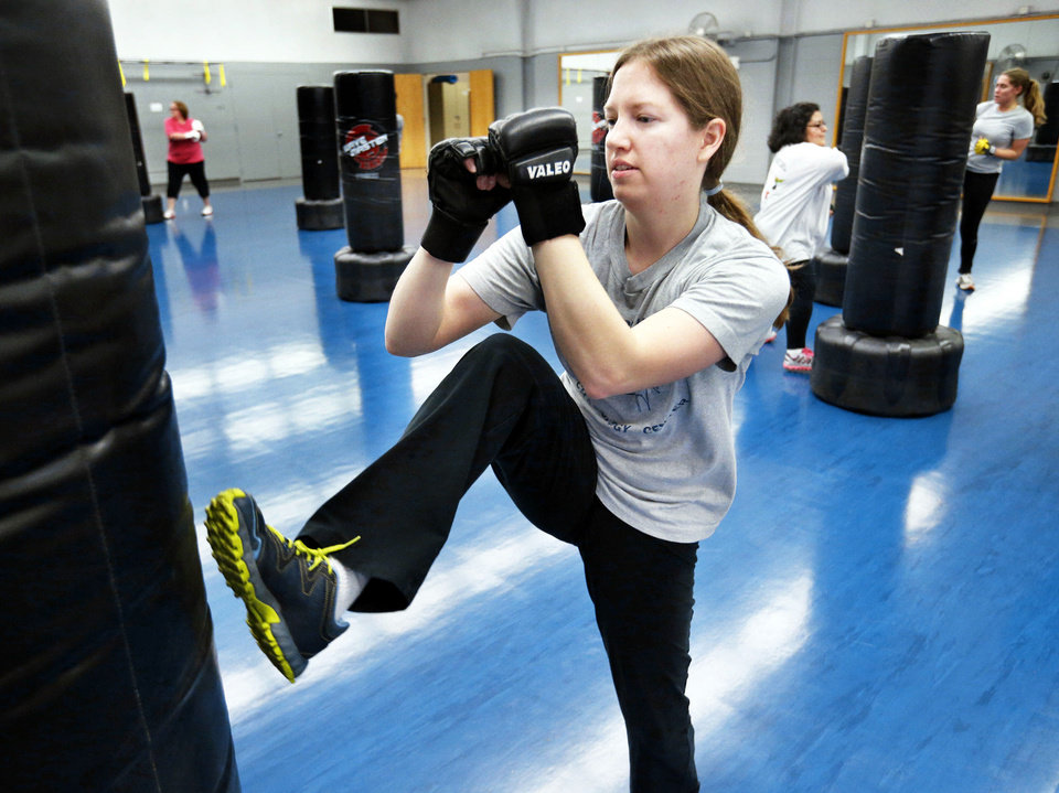 Lindsay Maass works out during a kickboxing class at the Huston Huffman Recreational Center on the  University of Oklahoma campus. PHOTOs BY STEVE SISNEY, THE OKLAHOMAN