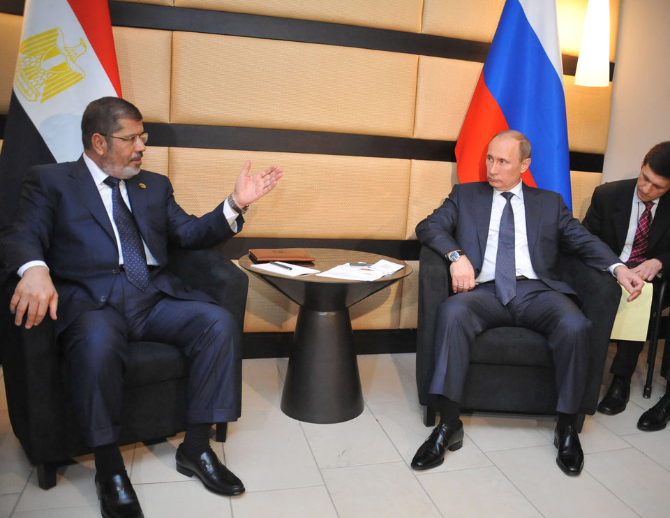 In this image released by the office of the Egyptian Presidency, Mohammed Morsi, left, meets with Russian President Vladimir Putin, right, during the BRICS 2013 Summit in Durban, South Africa, Wednesday, March 27, 2013. Heads of State of BRICS nations met in the South Africa city of Durban for the two-day summit. (AP Photo/Egyptian Presidency)