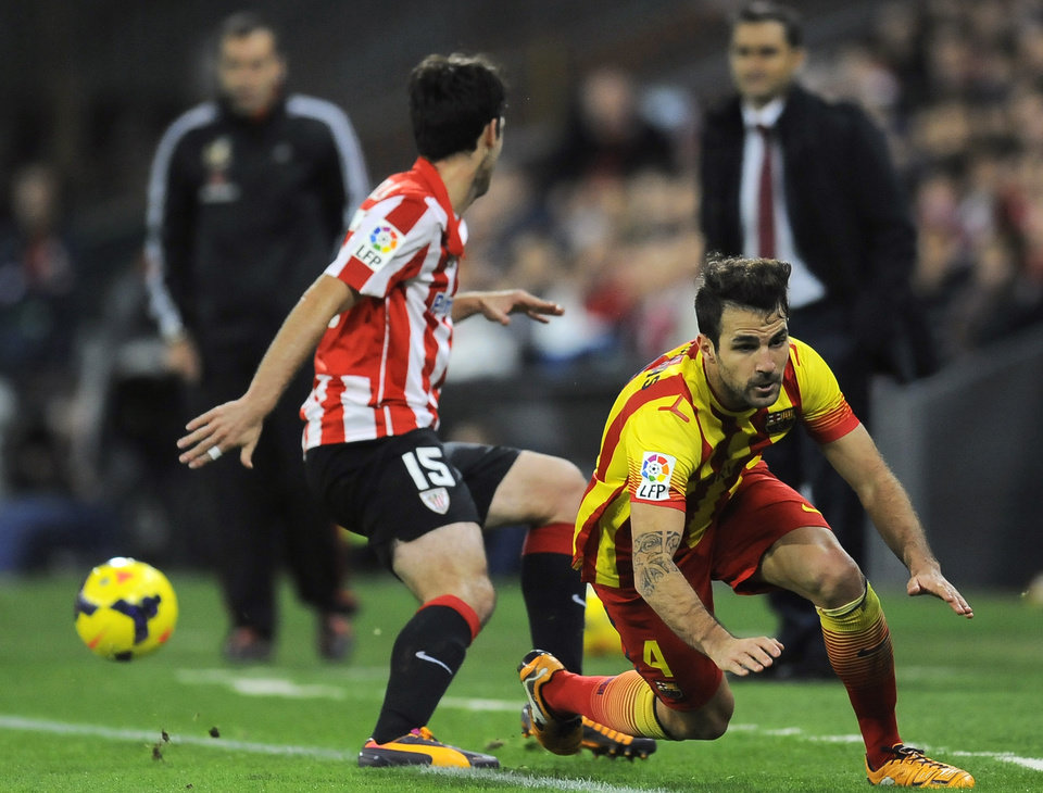 Barcelona's Francesc Fabregas, right, is tackled by Athletic Bilbao's Andoni Iraola during their Spanish League soccer match, at San Mames stadium in Bilbao, Spain, Sunday, Dec. 1, 2013. F.C. Barcelona lost the match 1-0. F.C. Barcelona lost the match 1-0.  (AP Photo/Alvaro Barrientos)