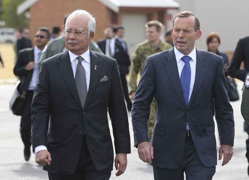 Photo - Malaysian Prime Minister Najib Razak, left, walks along the tarmac with Australian Prime Minister Tony Abbott on their way to meet crew members involved in search of wreckage and debris of the missing Malaysia Airlines MH370 in Perth, Australia, Thursday, April 3, 2014. Najib was in Australia to meet with Abbott to hold bilateral talks about the missing plane and to attend briefings with crew members. (AP Photo/Rob Griffith/Pool)