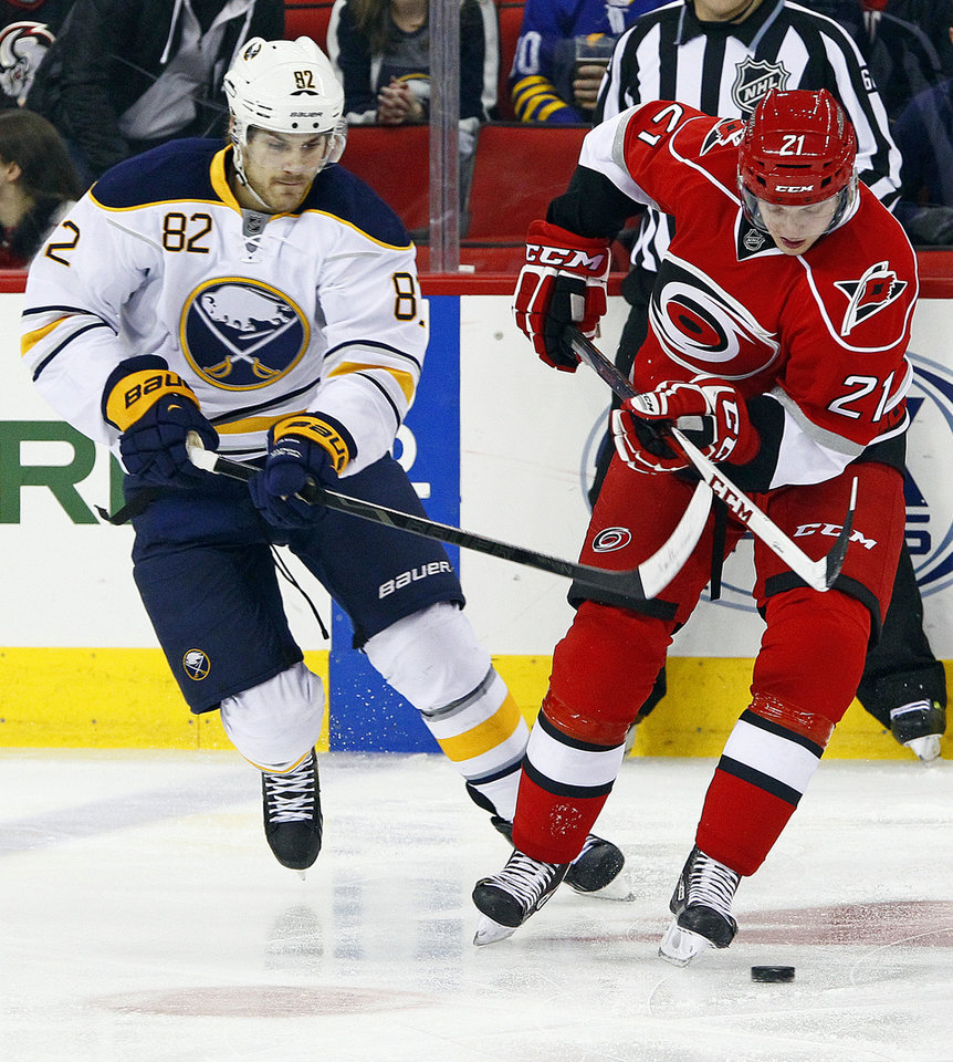 Carolina Hurricanes' Drayson Bowman (21) works the puck in front of Buffalo Sabres' Marcus Foligno (82) during the first period of an NHL hockey game, Tuesday, March 5, 2013, in Raleigh, N.C. (AP Photo/Karl B DeBlaker)