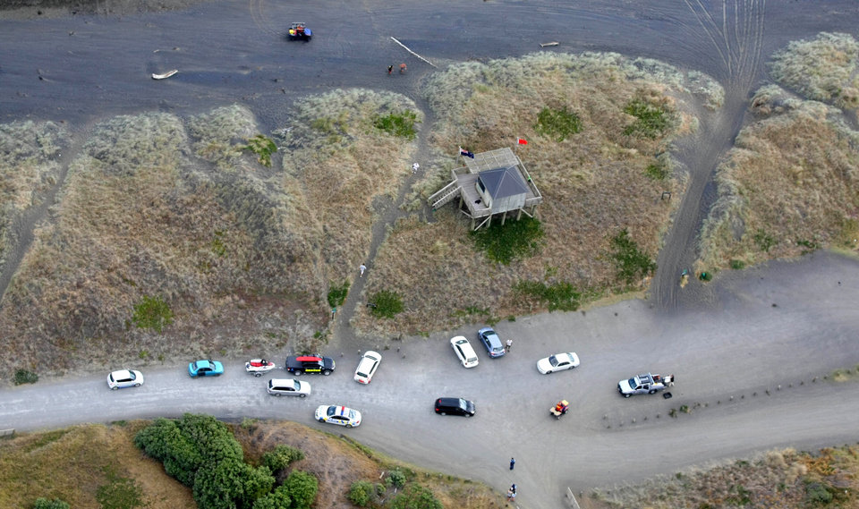 Photo - In this aerial photo, emergency vehicles are parked at Muriwai Beach near Auckland, New Zealand, Wednesday, Feb. 27, 2013, following a fatal shark attack. Police said a man was found dead in the water Wednesday afternoon after being