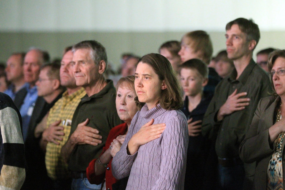 Photo - People look on during the national anthem at a rally of the Western Republican Leadership Conference, Friday, April 25, 2014, in Sandy, Utah. Republican U.S. Sen. Ted Cruz, of Texas, is scheduled to headline the final day of a two-day conference in Utah where Republican party leaders from western states are meeting. Speakers at the Western Republican Leadership Conference also include Utah's two U.S. senators, Mike Lee and Orrin Hatch, National Republican Party Chairman Reince Priebus, Utah Gov. Gary Herbert, Utah Attorney General Sean Reyes and Republican congressional candidate Mia Love. (AP Photo/Rick Bowmer)