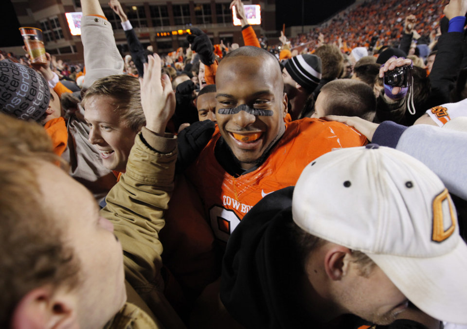Photo - OSU's Richetti Jones (99) makes his way through celebrating fans on the field after the Bedlam college football game between the Oklahoma State University Cowboys and the University of Oklahoma Sooners at Boone Pickens Stadium in Stillwater, Okla., Saturday, Dec. 3, 2011. OSU beat OU, 44-10. Photo by Nate Billings, The Oklahoman