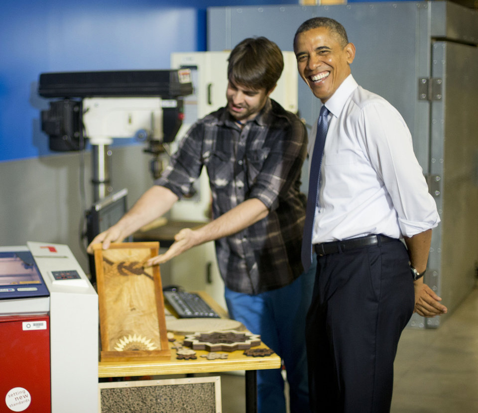 Photo - President Barack Obama smiles as he is shown wooden art made using a laser etcher  by James Gyre during his tour of TechShop, Tuesday, June 17, 2014, in Pittsburgh, Pa. Obama traveled to Pittsburgh and visited TechShop, a fabrication and prototyping studio open to the public via paid memberships, to deliver remarks on the economy. (AP Photo/Pablo Martinez Monsivais)